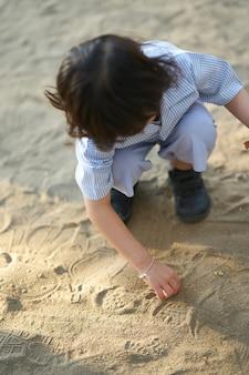 Het jonge geitje in de uniforme school van de studentenkleuterschool zit en speelt op zand