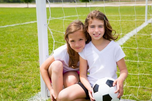 Het jonge geitjesmeisjes die van het voetbalvoetbal op gebied spelen