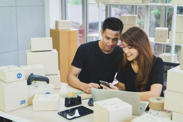Het jonge gelukkige aziatische bedrijfspaar is het werk samen gebruikend laptop, smartphone en tablet met een pakketdoos verpakking bij hun starthuiskantoor, van het mkb online bedrijf verkoper en leveringsconcept