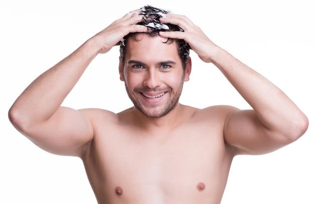 Het jonge gelukkige glimlachende haar van de mensenwas met shampoo - die op wit wordt geïsoleerd.