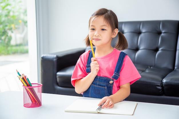 Het jonge gelukkige leuke aziatische meisje geniet van werkend aan haar schrijvend in haar huiswoonkamer