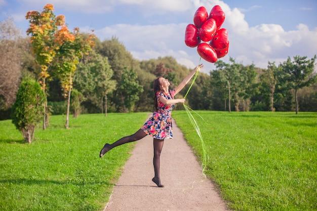 Het jonge gelukkige meisje in kleurrijke kleding heeft pret met rode buiten ballons