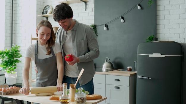 Het jonge gelukkige paar geniet en bereidt van gezonde maaltijd in hun keuken