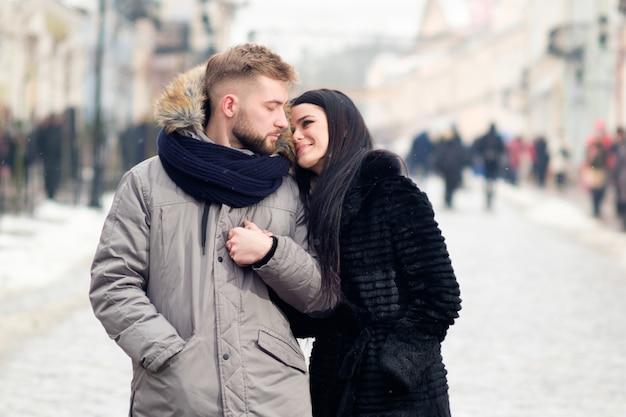 Het jonge gelukkige paar omhelst elkaar lopend in de straat van stad in de winter onder sneeuwval en het glimlachen