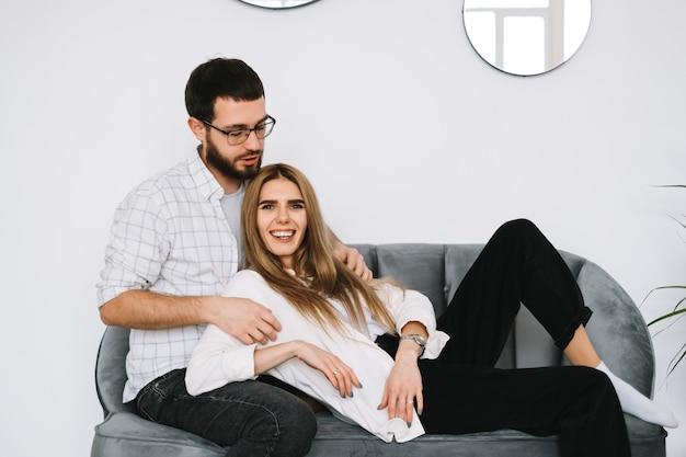 Het jonge gelukkige paar omhelst en rust thuis op een bank.