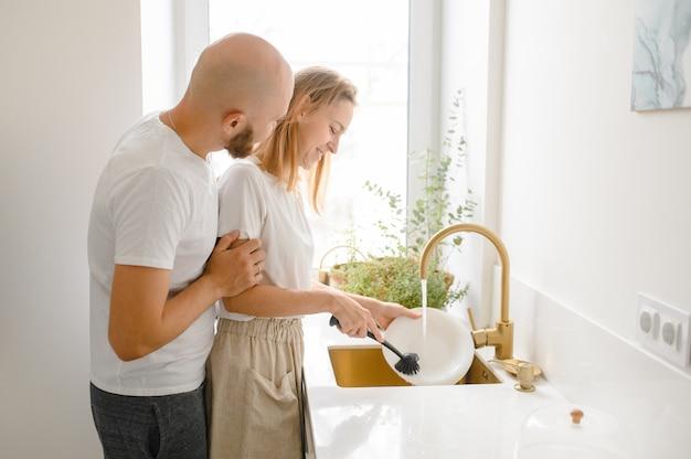 Het jonge gelukkige paar wast schotels terwijl thuis het schoonmaken doet