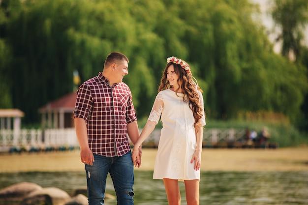 Het jonge gelukkige romantische zwangere paar loopt op aard dichtbij meer in de zomerpark. zwangere vrouw die een baby verwacht. toekomstige vader en moeder, familie. moederdag, vaderdag.