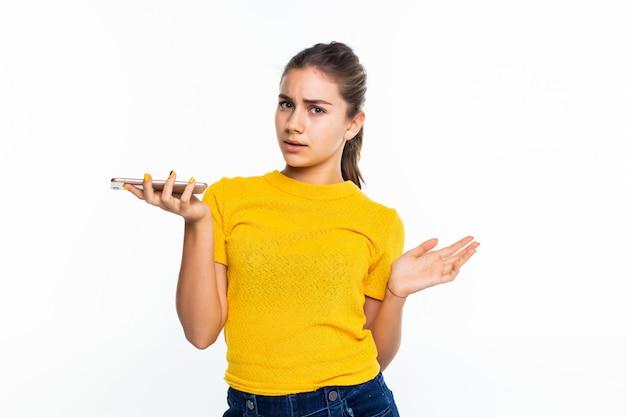 Het jonge gelukkige tienermeisje roept met een mobiele telefoon die op wit wordt geïsoleerd
