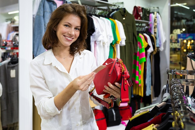 Het jonge gelukkige vrouw letten op bij prijsetiket van kleine rode zak in kledingswinkel
