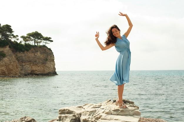 Het jonge gelukkige vrouw stellen dichtbij overzees