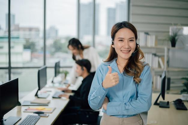 Het jonge gelukkige vrouwelijke call centre glimlacht en bekijkt camera.