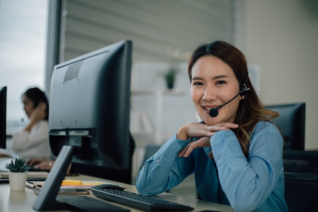 Het jonge gelukkige vrouwelijke callcenter glimlacht en bekijkt camera.