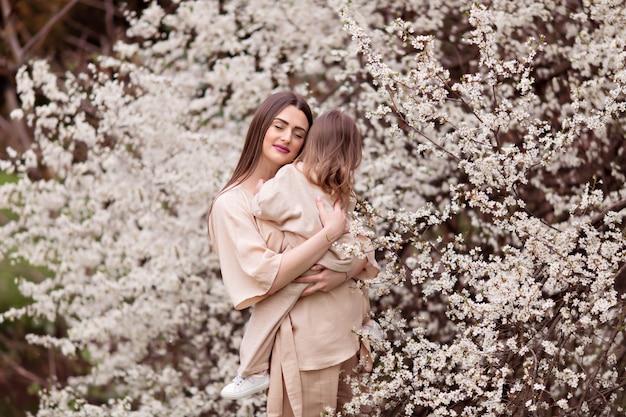 Het jonge gelukkige zwangere meisje koestert haar dochter op een achtergrond van bloeiende bomen.