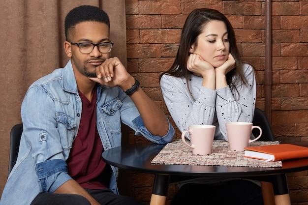 Het jonge gemengde raspaar heeft ruzie in cafetaria, ontstemde gelaatsuitdrukking, regelen relaties, drink warme koffie, praat niet met elkaar. ongelukkige multi-etnische liefhebbers in restaurant.