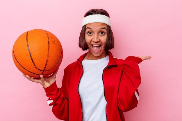 Het jonge gemengde speelbasketbal van de rasvrouw dat op roze muur wordt geïsoleerd die een exemplaarruimte op een palm toont en een andere hand op taille houdt.