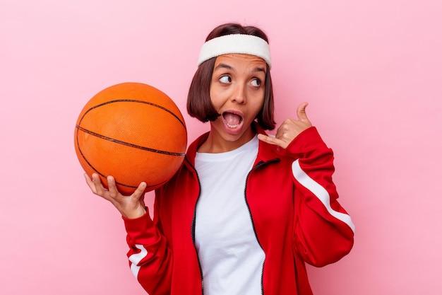 Het jonge gemengde speelbasketbal van de rasvrouw dat op roze muur wordt geïsoleerd die een mobiel telefoongesprekgebaar met vingers toont.