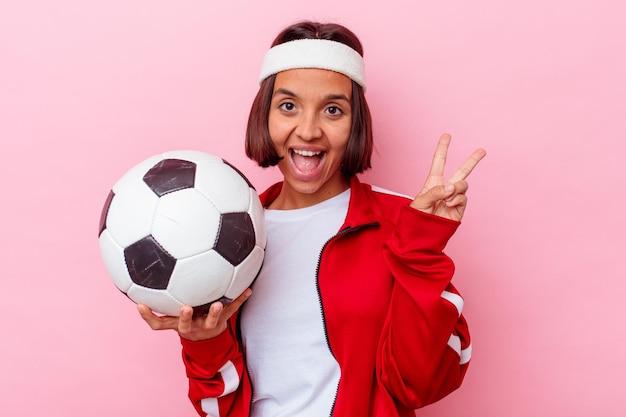 Het jonge gemengde speelvoetbal van de rasvrouw dat op roze muur vrolijk en zorgeloos wordt geïsoleerd die een vredessymbool met vingers toont.