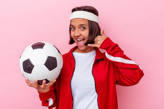 Het jonge gemengde speelvoetbal van de rasvrouw dat op roze muur wordt geïsoleerd die een mobiel telefoongesprekgebaar met vingers toont.