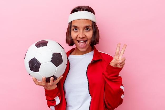 Het jonge gemengde speelvoetbal van de rasvrouw dat op roze muur wordt geïsoleerd die nummer twee met vingers toont.