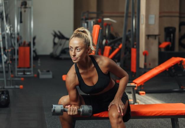 Het jonge geschiktheidsvrouw doen geconcentreerd het doen van domoorliften voor bicepsen één hand terwijl het zitten op een bank in de gymnastiek. trainingsconcept met vrije gewichten.