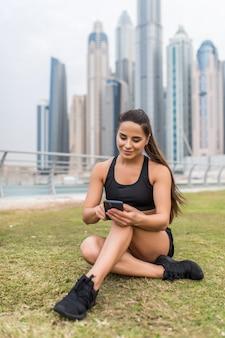 Het jonge geschiktheidsvrouw typen op telefoon terwijl het zitten en ontspant op wolkenkrabbersruimte