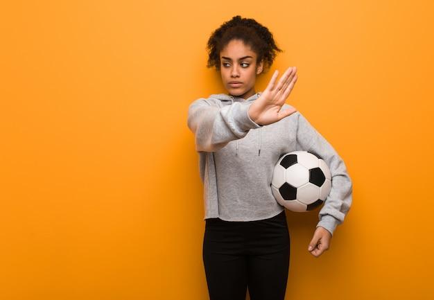 Het jonge geschiktheidszwarte zetten dient voorzijde in. een voetbal vasthouden.