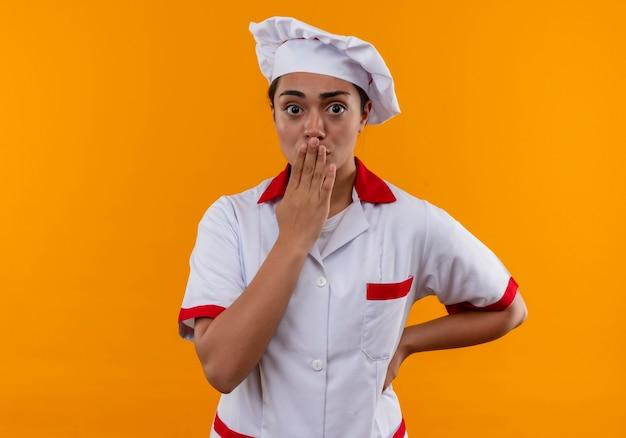 Het jonge geschokte kaukasische kokmeisje in eenvormige chef-kok legt hand op mond die op oranje muur wordt geïsoleerd