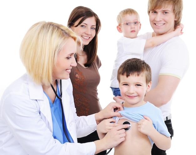 Het jonge gezin met twee zoontjes op de medische receptie van de jonge vrouwelijke arts