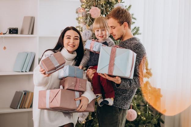 Het jonge gezin met zoontje door kerstboom met kerstcadeautjes