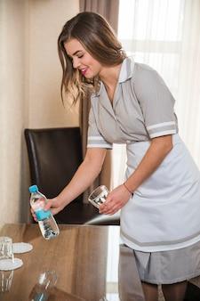 Het jonge glas van de kamermeisjesholding en fles water die over de houten lijst plaatsen
