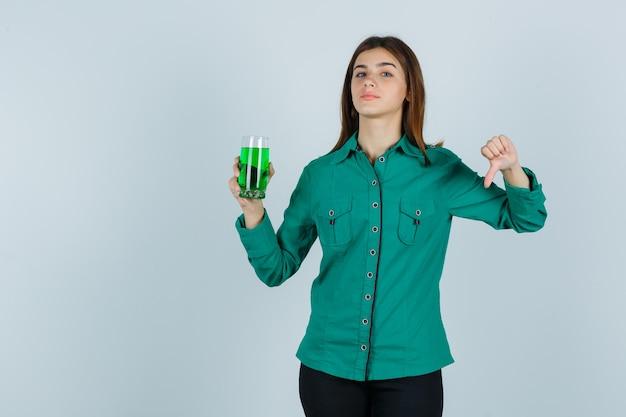 Het jonge glas van de meisjesholding van groene vloeistof, die duim in groene blouse, zwarte broek toont en ontevreden kijkt. vooraanzicht.
