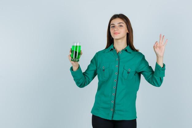 Het jonge glas van de meisjesholding van groene vloeistof, toont ok teken in groene blouse, zwarte broek en kijkt vrolijk. vooraanzicht.