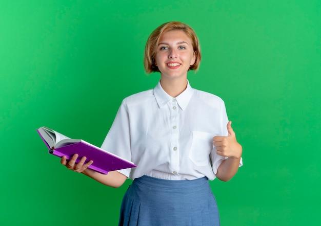 Het jonge glimlachende blonde russische meisje beduimelt omhoog en houdt boek dat op groene achtergrond met exemplaarruimte wordt geïsoleerd