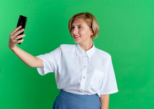 Het jonge glimlachende blonde russische meisje bekijkt telefoon die op groene achtergrond met exemplaarruimte wordt geïsoleerd