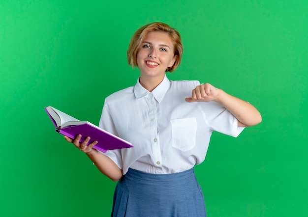 Het jonge glimlachende blonde russische meisje houdt boek en wijst naar zichzelf geïsoleerd op groene achtergrond met exemplaarruimte