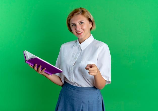 Het jonge glimlachende blonde russische meisje houdt boek wijzend op camera die op groene achtergrond met exemplaarruimte wordt geïsoleerd