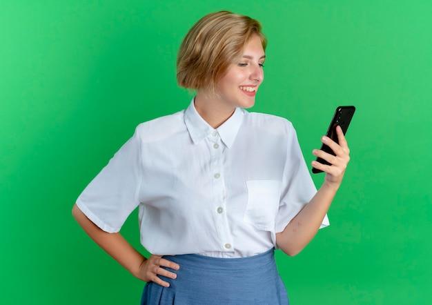 Het jonge glimlachende blonde russische meisje houdt en bekijkt telefoon die op groene achtergrond met exemplaarruimte wordt geïsoleerd