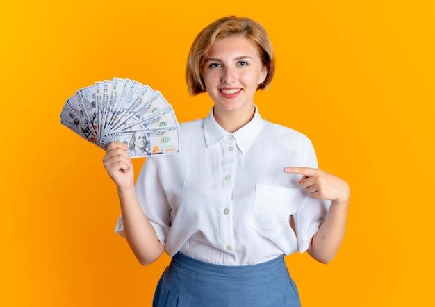 Het jonge glimlachende blonde russische meisje houdt en wijst op geld dat op oranje achtergrond met exemplaarruimte wordt geïsoleerd