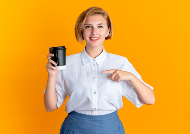 Het jonge glimlachende blonde russische meisje houdt en wijst op koffiekop die op oranje achtergrond met exemplaarruimte wordt geïsoleerd