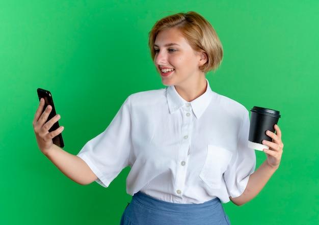 Het jonge glimlachende blonde russische meisje houdt koffiekop die telefoon bekijkt die op groene achtergrond met exemplaarruimte wordt geïsoleerd