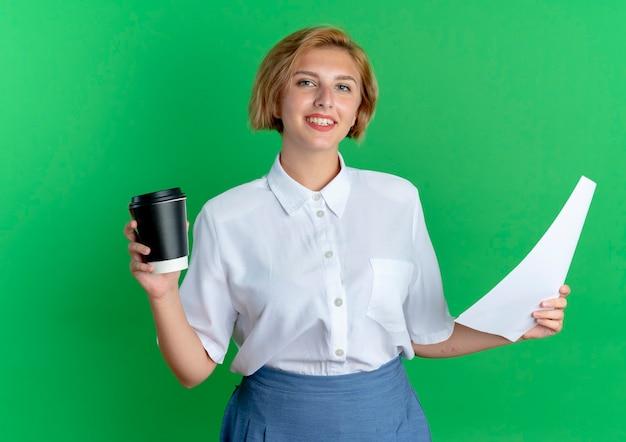 Het jonge glimlachende blonde russische meisje houdt koffiekop en vellen papier die op groene achtergrond met exemplaarruimte worden geïsoleerd