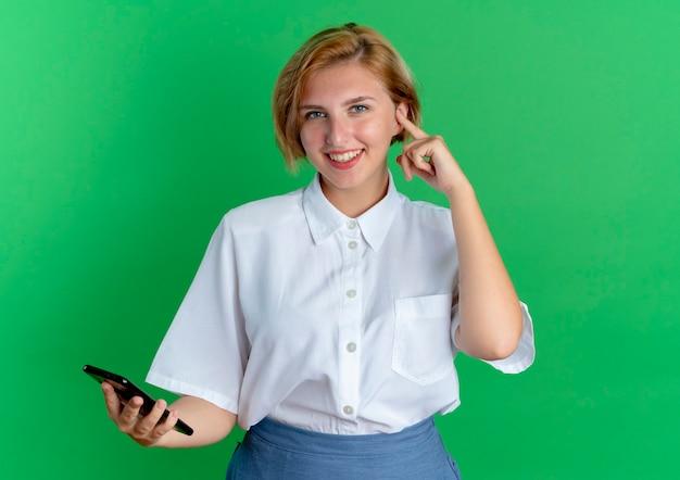 Het jonge glimlachende blonde russische meisje houdt telefoon en legt vinger op oor dat op groene achtergrond met exemplaarruimte wordt geïsoleerd