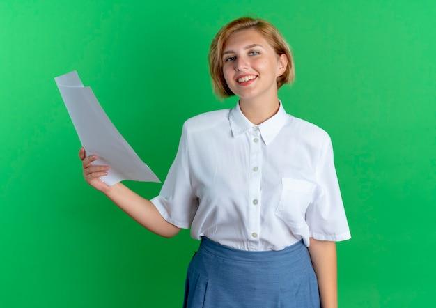 Het jonge glimlachende blonde russische meisje houdt vellen papier die op groene achtergrond met exemplaarruimte worden geïsoleerd