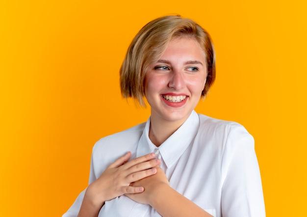 Het jonge glimlachende blonde russische meisje legt handen op borst die kant bekijken die op oranje achtergrond met exemplaarruimte wordt geïsoleerd