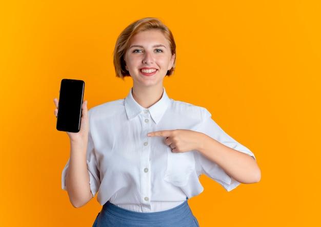 Het jonge glimlachende blonde russische meisje richt op telefoon die op oranje achtergrond met exemplaarruimte wordt geïsoleerd