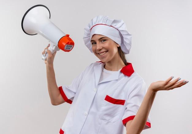 Het jonge glimlachende kaukasisch kokmeisje in eenvormige chef-kok houdt luide spreker en houdt hand open op wit met exemplaarruimte