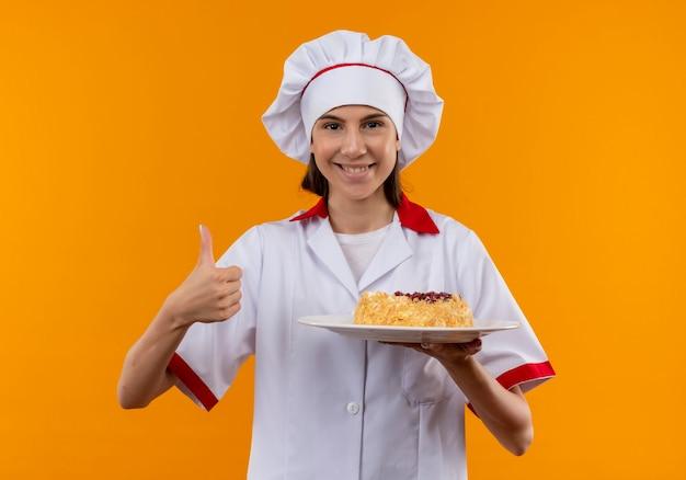 Het jonge glimlachende kaukasische kokmeisje in eenvormige chef-kok houdt cake op plaat en duimen omhoog geïsoleerd op oranje achtergrond met exemplaarruimte