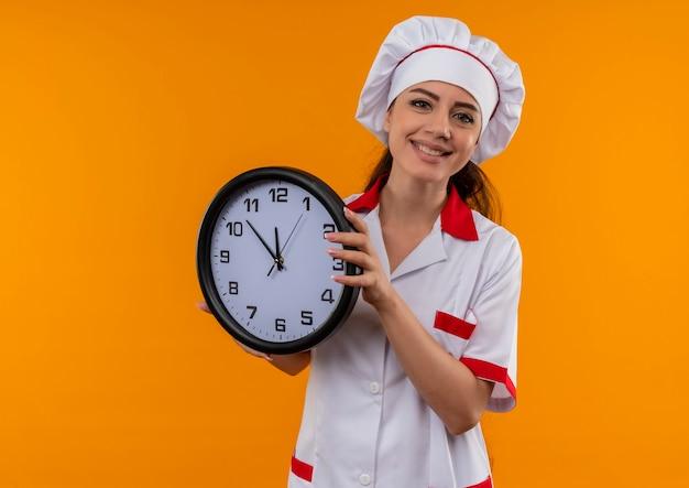 Het jonge glimlachende kaukasische kokmeisje in eenvormige chef-kok houdt klok die op oranje muur met exemplaarruimte wordt geïsoleerd
