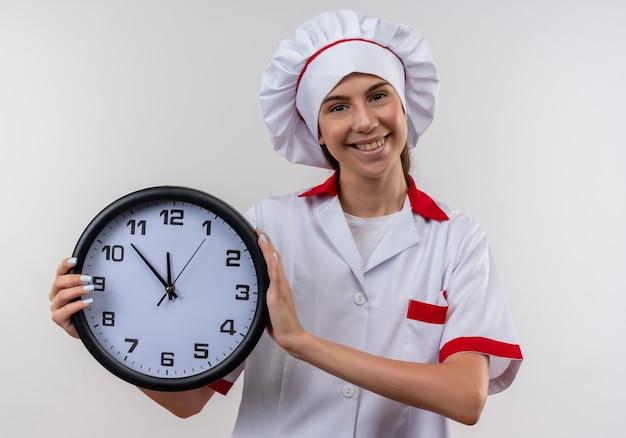 Het jonge glimlachende kaukasische kokmeisje in eenvormige chef-kok houdt klok op wit met exemplaarruimte