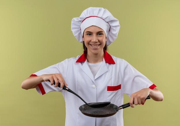Het jonge glimlachende kaukasische kokmeisje in eenvormige chef-kok houdt koekenpan en spatel die op groene achtergrond met exemplaarruimte wordt geïsoleerd